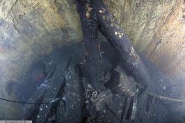Fundsituation der aufgrund der Bombardierungen Ende des II. Weltkrieges verbrannten sowie in den Brunnenschacht gestürzten Eichenbalken am Schachtgrund des Tiefen Brunnen (April 2012); Foto: U. Kunz/Kiel.