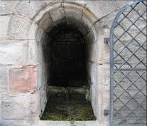 Der heute durch ein massives Eisengitter verschlossene Eingang zur Quellkammer des Margarethenbrunnen ca. 20 m SE' des Tiefen Brunnen.