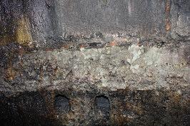 Paarweise auftretende, annähernd quadratische Rüstlöcher im anstehenden Fels der E' Schachtwand des Tiefen Brunnen der Nürnberger Kaiserburg. Foto: Florian Huber/Kiel.
